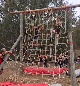 people climbing up a net on fitness bootcamp holiday